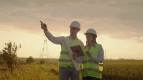 De techniek die aan toren Met hoog voltage werken, controleert de informatie over tabletcomputer twee werknemersman en vrouw stock footage