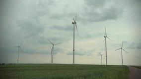 De technologievuurraderen van het windpark op een landbouwcornfield landschap met bewolkte hemel stock video