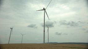 De technologievuurraderen van het windpark op een landbouwcornfield landschap met bewolkte hemel stock footage