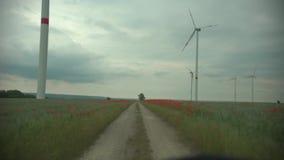 De technologievuurraderen van het windpark op een landbouwcornfield landschap met bewolkte hemel stock videobeelden