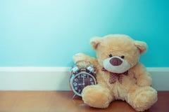 De teddybeer die de glanzende klok, tijd houden is omhoog, is de tijd beperkt stock afbeelding
