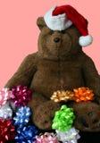 De Teddybeer die van Kerstmis de Hoed van de Kerstman met Roze Achtergrond draagt Royalty-vrije Stock Foto's
