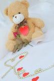 De teddybeer met rood hart en rood nam toe Stock Foto's