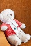 De teddybeer ontspant op bruine bank Stock Foto's