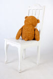 De teddybeer zit op een stoel Stock Foto's