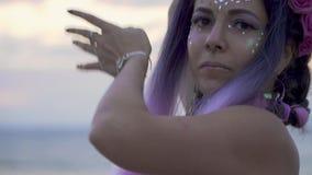 De tedere jonge vrouw met het fonkelen make-up doordrong neus in een roze kleding die in openlucht dansen De dans van een sensuee stock video