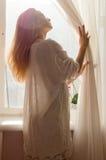 De tedere vrij jonge blonde vrouw status dichtbij venster thuis of hotelruimte en het welig tieren in het zonlicht flakkeren Royalty-vrije Stock Foto