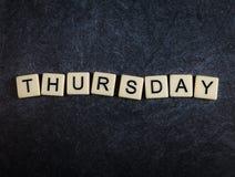 De tegels van de scrabblebrief op zwarte lei achtergrondspellingsdonderdag stock afbeelding