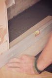 De tegelzetter installeert keramische tegels Stock Foto's