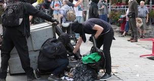 De tegen-protesteerders beginnen brand in afvalbak tijdens een protest stock footage