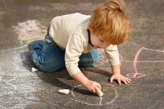 De tekening van de jongen buiten met krijt Royalty-vrije Stock Foto