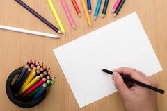 De tekening van de meisjeshand Leeg document en kleurrijke potloden op houten lijst stock foto