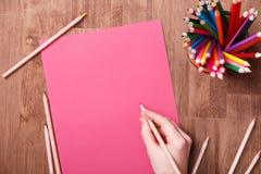 De tekening van de meisjeshand, leeg roze document en kleurrijke potloden op houten lijst Stock Foto