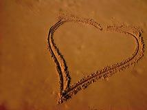 De tekening van een hart op zandig is royalty-vrije stock afbeeldingen