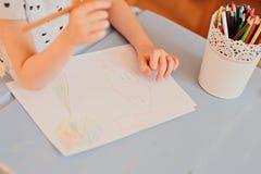 De tekening van het kindmeisje met kleurenpotloden thuis Stock Afbeeldingen