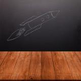 De tekening van kinderen een raket op een bord achter een houten tabl Stock Foto's
