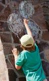 De tekeningsballons van de jongen op een steenmuur Stock Foto