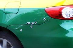 De tekens bullets gat op de autobonnet, het gebarsten gat van de granaatscherfkogel schot op autooppervlakte, schieten de auto stock fotografie