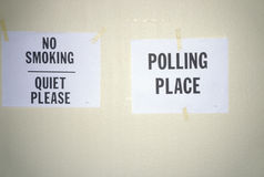 De tekens die aan de muur in een stemlokaal worden vastgebonden lezen Nr - het roken en Stemlokaal Royalty-vrije Stock Foto