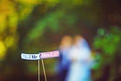 De tekens lezen M. en Mevr. of M. en Mevr bij een huwelijksontvangst boven de bruid en de bruidegom, zijn de gelukkige minnaars b royalty-vrije stock fotografie