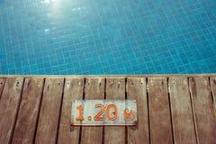 De tekens of de tellers van de zwembaddiepte op houten vloer naast blauwe waterpool die worden gevestigd stock fotografie