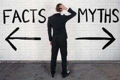 De Tekens van zakenmanlooking at arrow onder Feiten en Mythen stock afbeelding