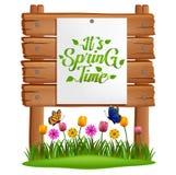De tekst het de lentetijd van ` s op papier plakte aan een houten raad met gras en bloemen stock illustratie