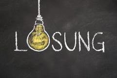 De tekst van 'Lösung 'met een idee gloeilamp op schoolbord Vertaling: 'Oplossing ' stock illustratie