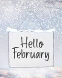De tekst van Hello Februari op de witte banner van de plaatraad met koude sneeuw F royalty-vrije stock afbeeldingen