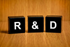 De tekst van R&D of van het Onderzoek en van de ontwikkeling op zwart blok stock foto's