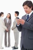 De tekstbericht van de verkoperslezing op cellphone met team achter hem Stock Foto