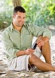 De tekstoverseinen van de mens op celtelefoon bij strand Royalty-vrije Stock Foto's