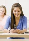 De tekstoverseinen van de student op celtelefoon in klaslokaal Royalty-vrije Stock Foto's