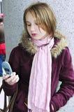 De tekstoverseinen van de tiener op celtelefoon Stock Foto's