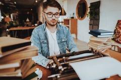 De tekstschrijver Working op Schrijfmachine zit bij Bureau royalty-vrije stock foto's