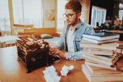 De tekstschrijver Working op Schrijfmachine zit bij Bureau stock afbeelding