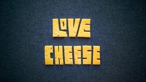 De tekstwoord van de liefdekaas op donkere achtergrond Snijd gele cheddar i royalty-vrije stock foto