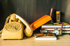 De telefoon en de kantoorbehoeften op bureau stock afbeelding