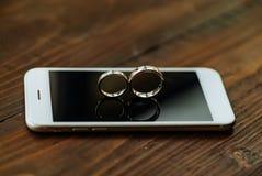 De telefoon is op een houten lijst De trouwringen in de vorm van acht is op het scherm van de telefoon in de ruimte stock foto
