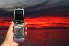 De telefoon van de cel bij zonsondergang Stock Foto's