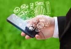 De telefoon van de handholding met hand getrokken toespraakbellen Royalty-vrije Stock Foto's