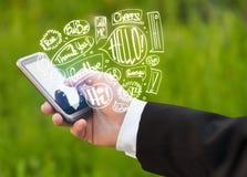 De telefoon van de handholding met hand getrokken toespraakbellen Royalty-vrije Stock Afbeeldingen