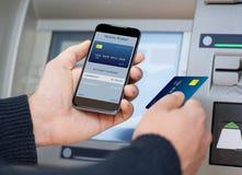 De telefoon van de mensenholding met mobiele portefeuille bij ATM Royalty-vrije Stock Foto