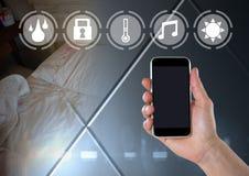 De telefoon van de handholding met slimme huisinterface thuis Stock Fotografie