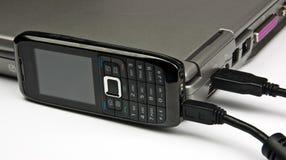 De telefoon van het concept die aan laptop via usbkabel wordt aangesloten Stock Foto's