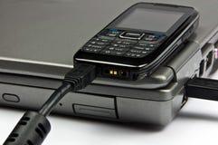 De telefoon van het concept die aan laptop via usbkabel wordt aangesloten Stock Afbeeldingen