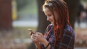 De Telefoon van het tienergebruik in Park stock footage