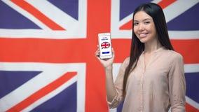 De telefoon van de meisjesholding met leert Engelse toepassing, vlag op achtergrond, onderwijs stock video