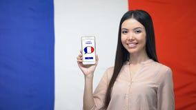 De telefoon van de meisjesholding met leert Franse toepassing, vlag op achtergrond, onderwijs stock footage
