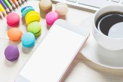De telefoon witte schermen, toetsenborden en makarons, koffiekop op de lijst Royalty-vrije Stock Fotografie